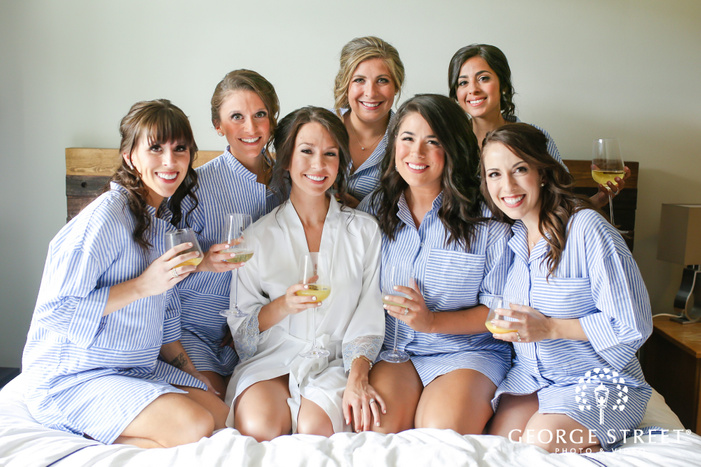 beautiful bride and bridesmaids on bed in bridal suite wedding photography