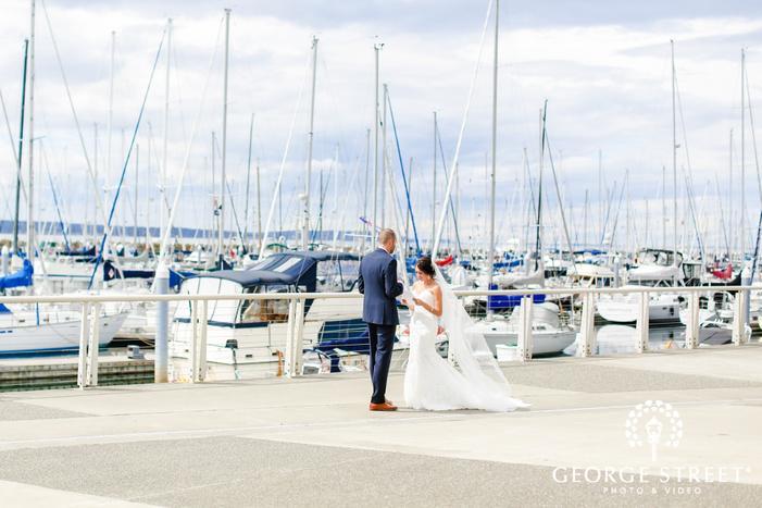sweet bride and groom on marina at ballard bay club in seattle