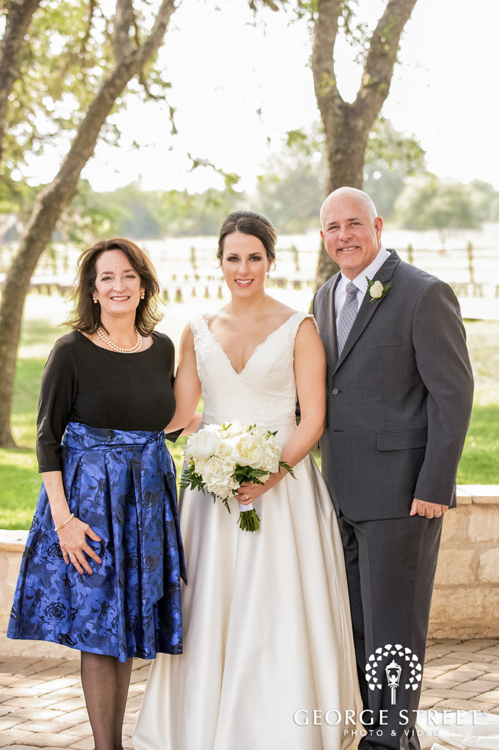 blissed bride and parents on pathway of wedding venue wedding photography