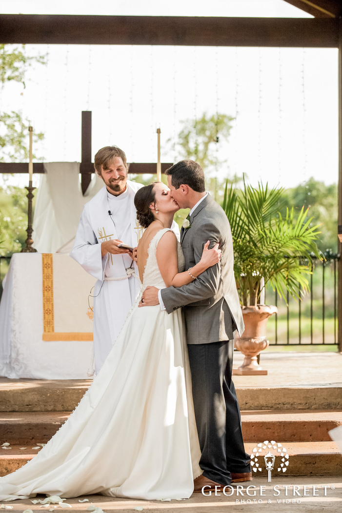 romantic bride and groom first kiss at altar wedding photo