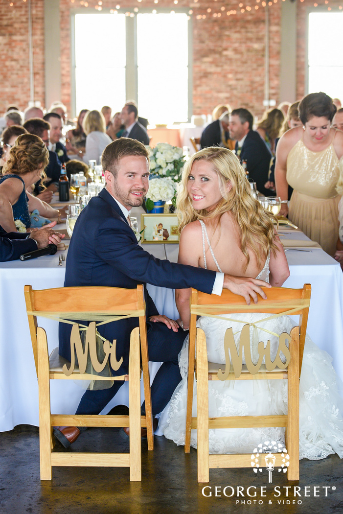 loving bride and groom on reception table wedding photos