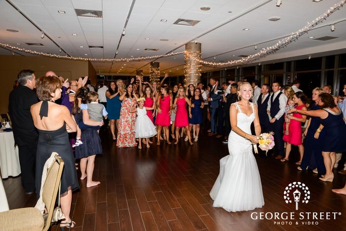 happy bride and friends bouquet toss on dance floor wedding photography