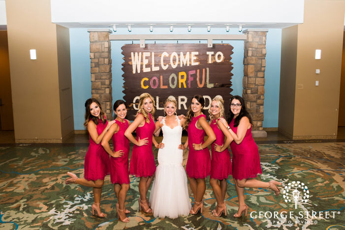 pretty bride and bridesmaids with artistic board in lobby wedding photography