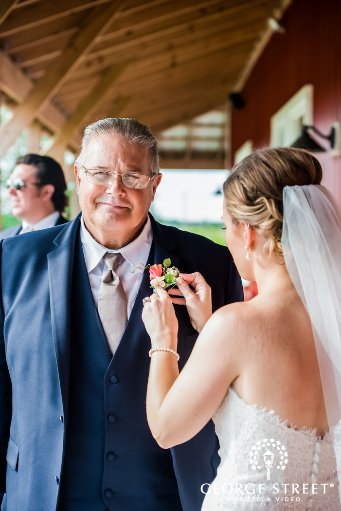 beautiful bride putting boutonniere to father
