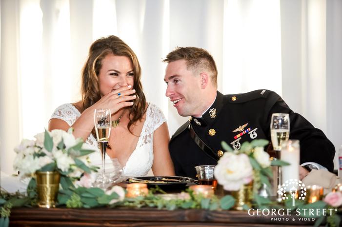 happy bride and groom onn reception table wedding photo