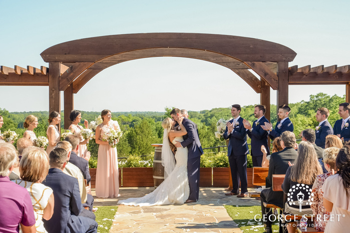 romantic bride and groom first kiss at stone crest venue in dallas fort worth