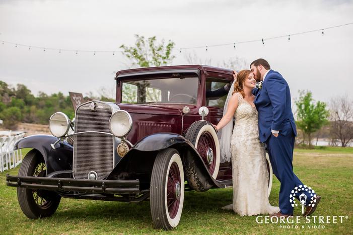 loving bride and groom near car in field wedding photography