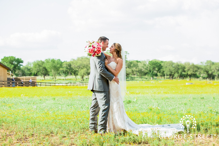 blissful bride and groom in the field at king river in austin wedding photography