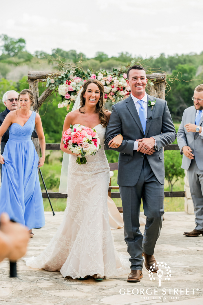 excited bride and groom exit from ceremony in austin wedding photo