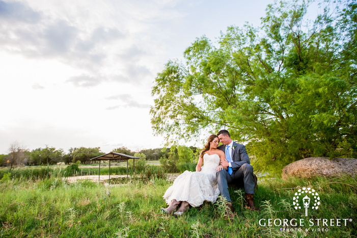 loving bride and groom in green field at king river in austin wedding photography