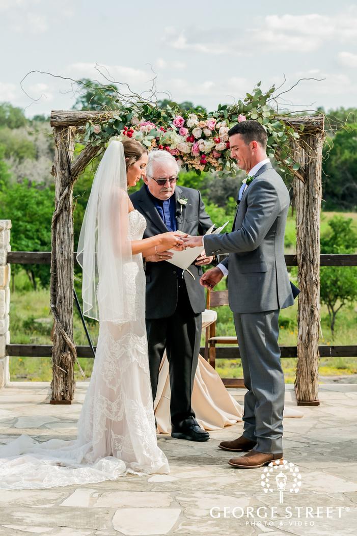 loving bride and groom wedding rings exchange at altar in austin wedding photo