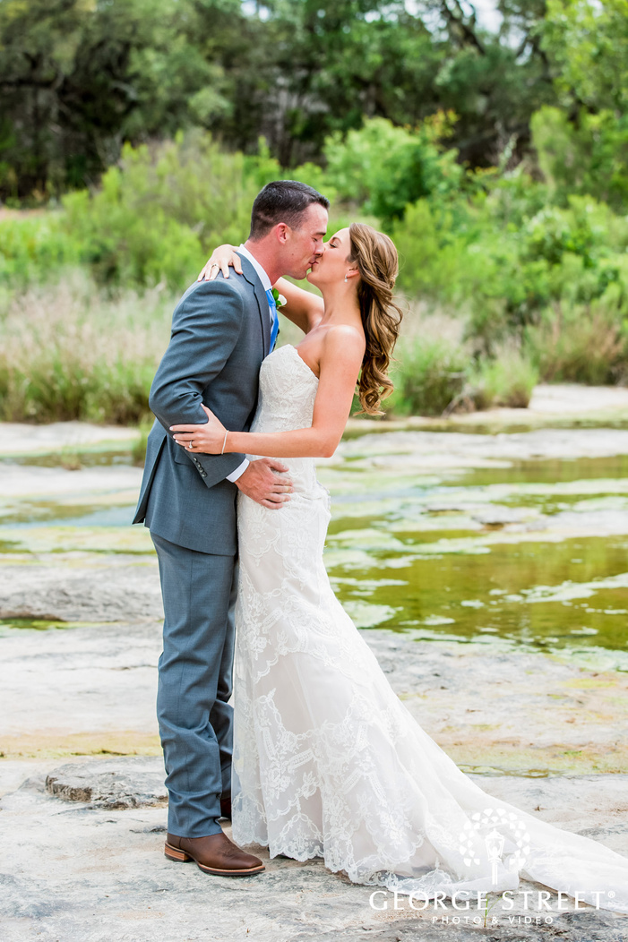 romantic bride and groom in the field at king river in austin wedding photography