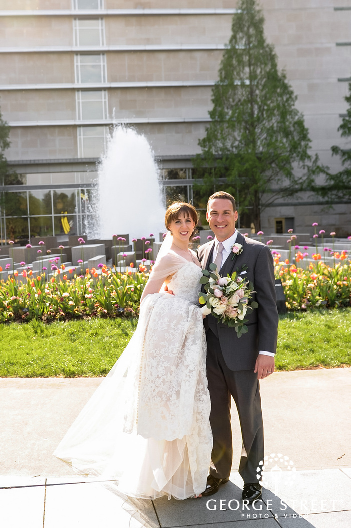 happy bride and groom in front of fountain and garden wedding photography