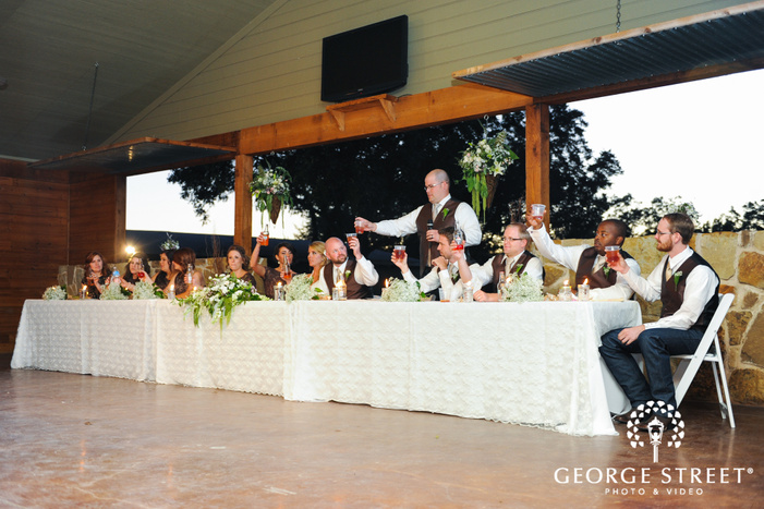 bridal party toasts at wedding reception head table