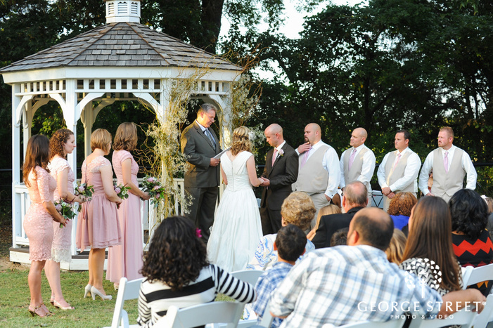 bridal party with bride and groom in front of gazebo during outdoor wedding ceremony