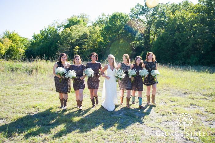 bride and bridesmaids in black lace dresses walking through empty field