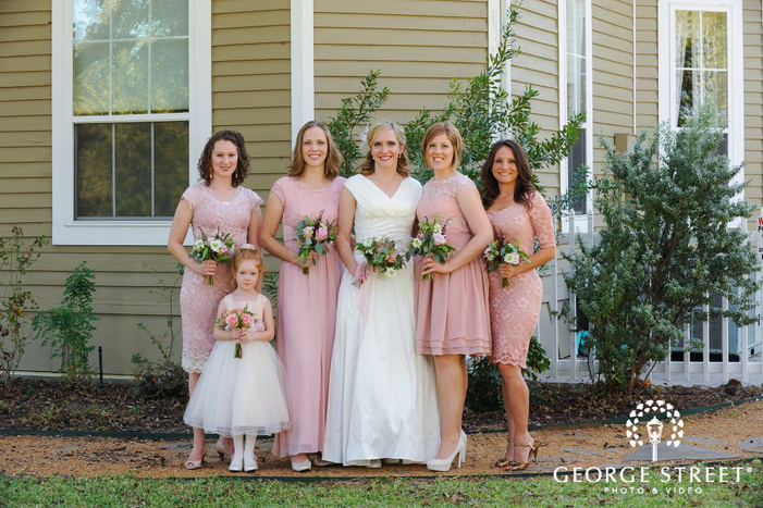 bride and bridesmaids in blush pink dresses with flower girl smiling with bouquets in front of house