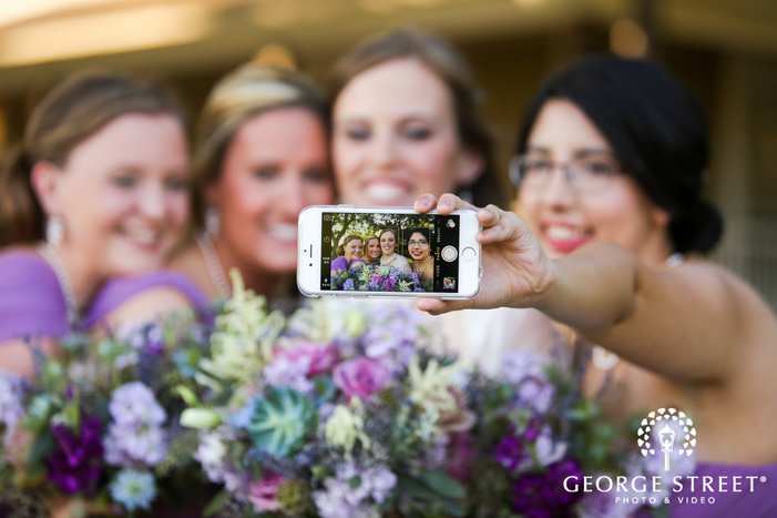 bride and bridesmaids taking selfie photo with iphone outdoors