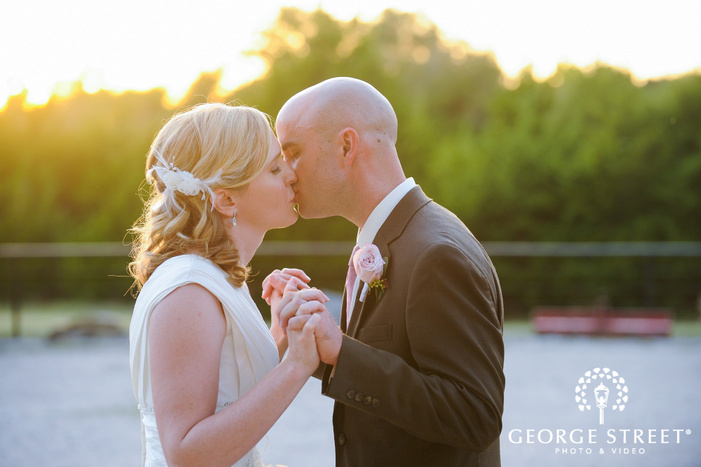 bride and groom holding hands and kissing in sunlight during golden hour