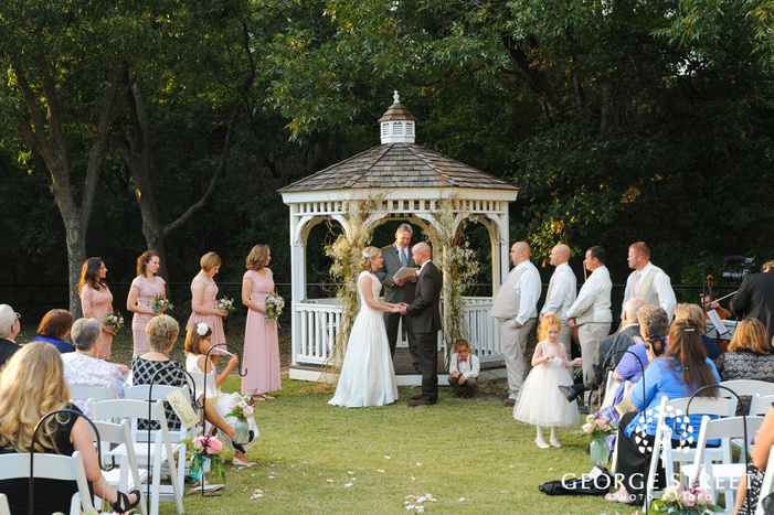 bride and groom holding hands in front of gazebo at outdoor wedding ceremony
