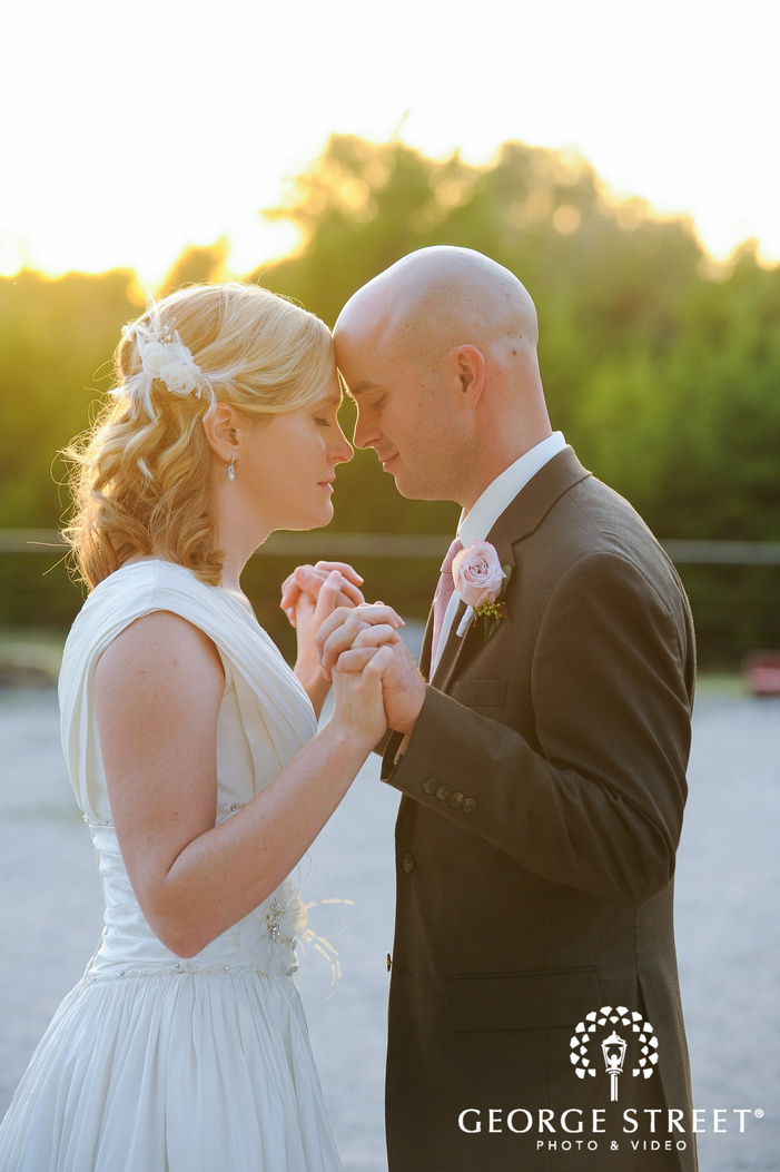 bride and groom holding hands in sunlight during golden hour