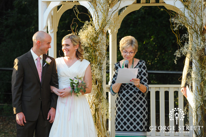 bride and groom smiling at each other during wedding ceremony outdoors