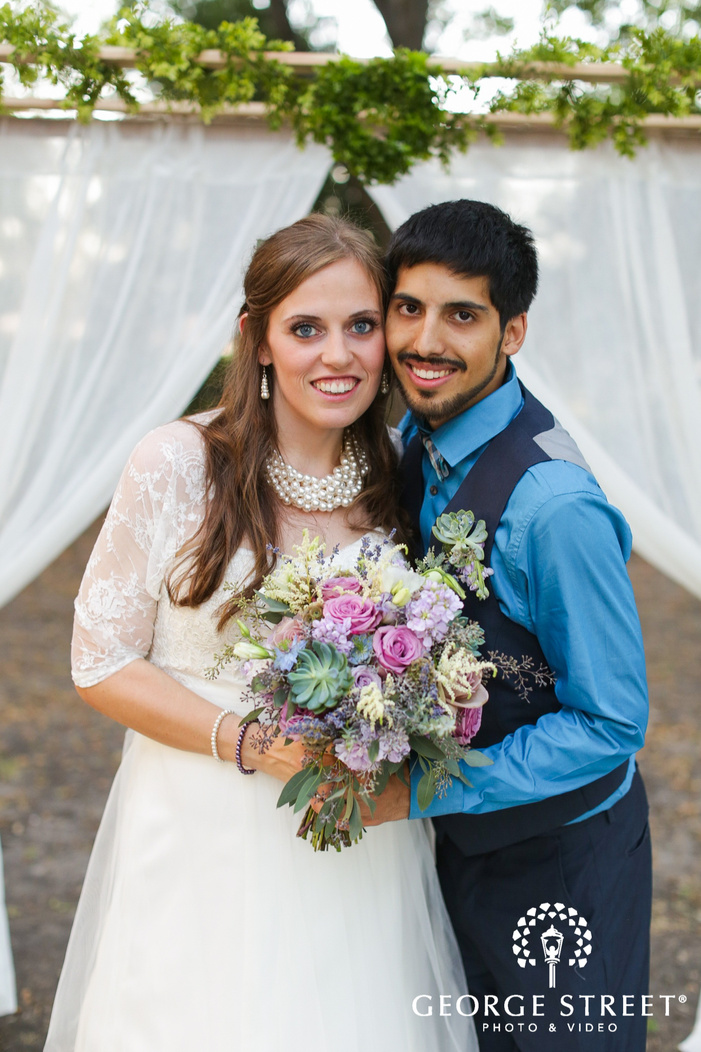 bride and groom with bouquet outdoors smiling