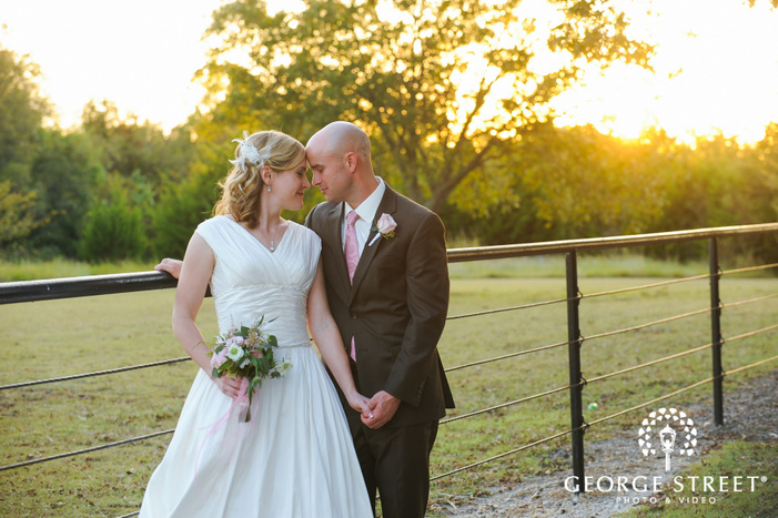 bride and groom with heads touching in front of sunny field during golden hour
