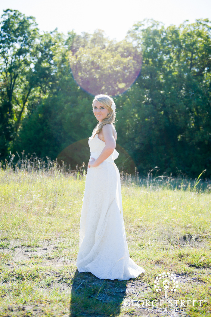 bride posing in sunny open field with sunflare