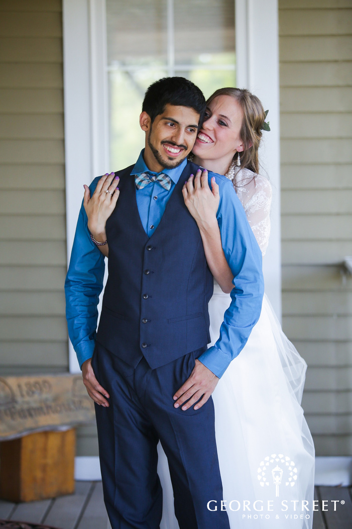bride smiling with groom on front porch