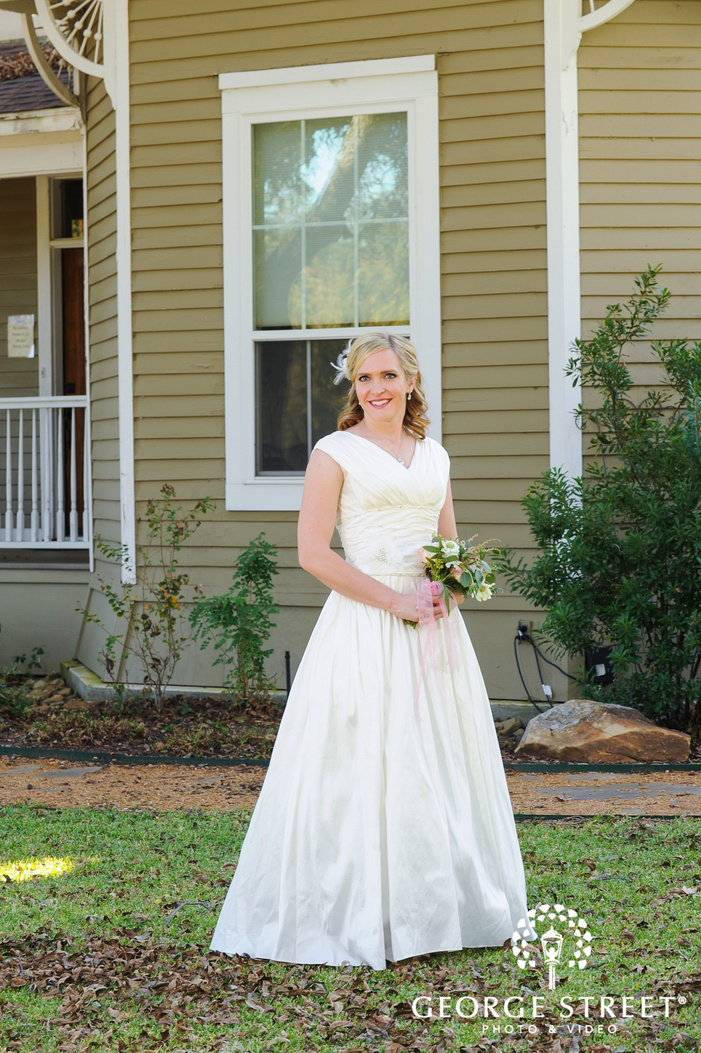 bride standing with bouquet in fall leaves in front of house