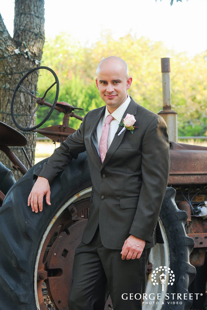 groom leaning against rusty tractor
