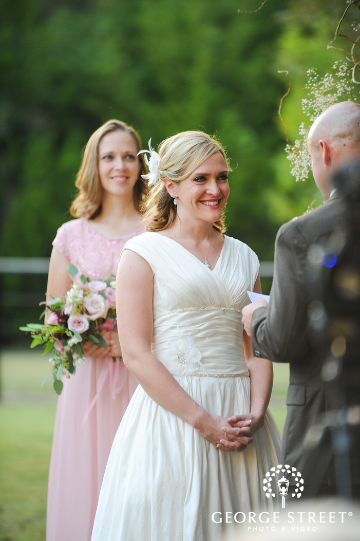 groom reading vows to smiling bride in outdoor wedding ceremony