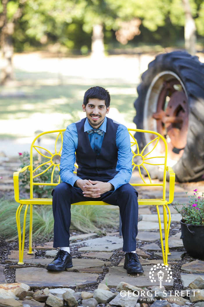groom sitting on yellow bench outside by tractor