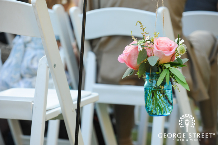 pink flowers in a blue mason jar details in outdoor wedding ceremony