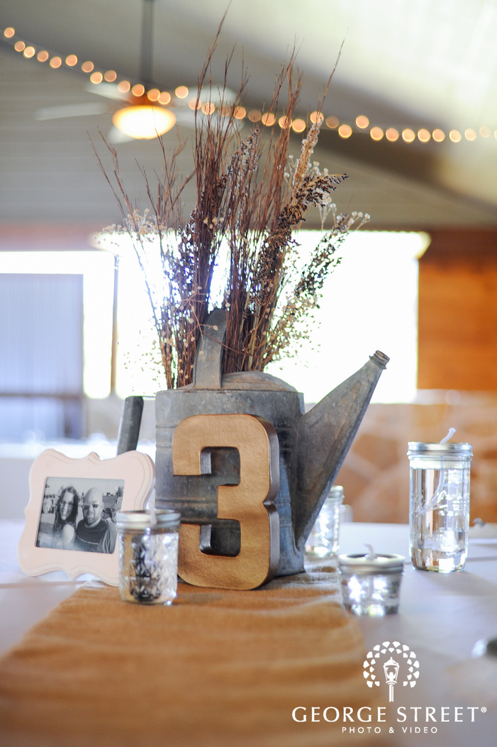 rustic water pot with branches reception table centerpiece details