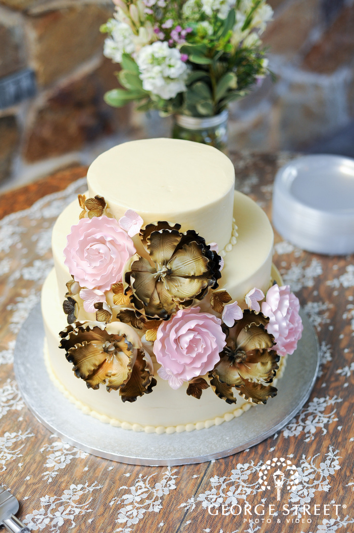 wedding cake with sugar flowers on lace tablecloth