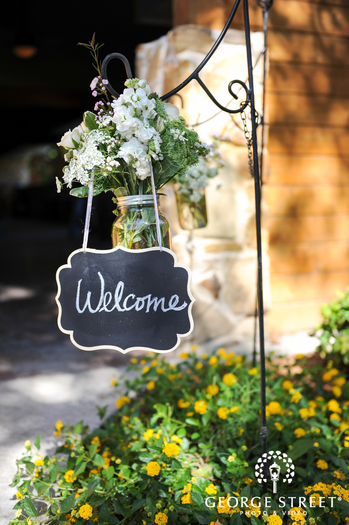 welcome sign outdoors with flowers and mason jar