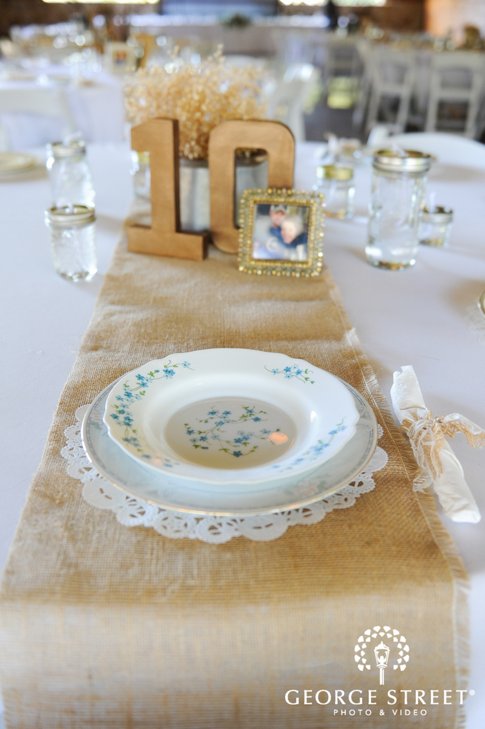 white floral plate on white and gold wedding reception table decor with burlap