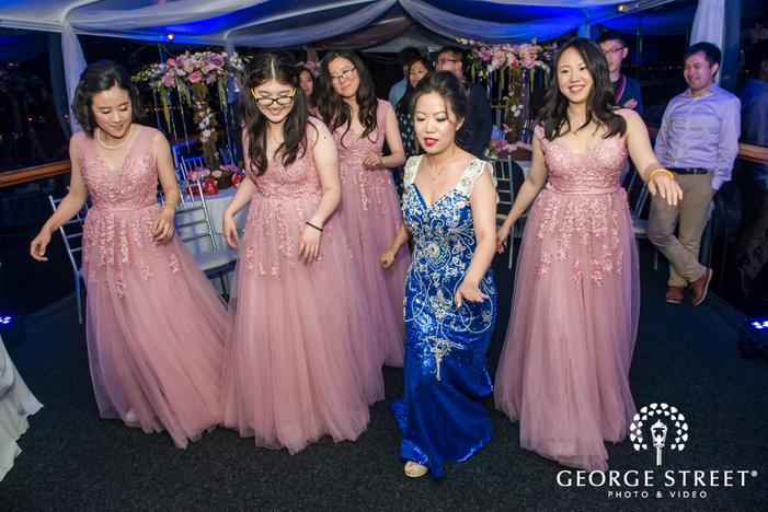 joyful bride and bridesmaids at reception dance