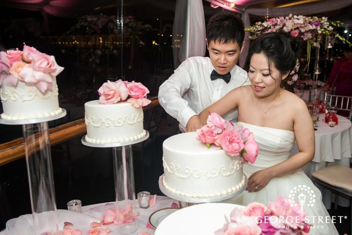 joyful bride and groom at cake cutting ceremony