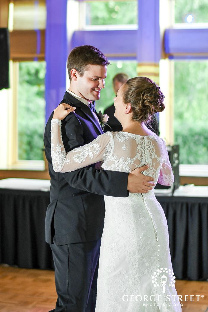 joyful bride and groom first dance in reception hall wedding photos