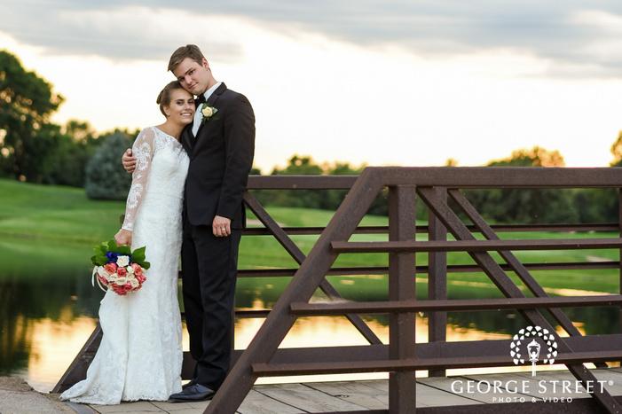 loving bride and groom on bridge near edinburgh golf course in minneapolis wedding photography