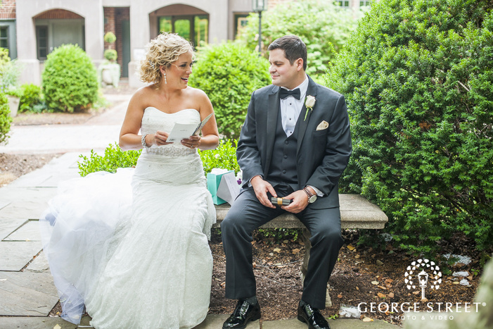 bride and groom exchanging gifts on stone bench
