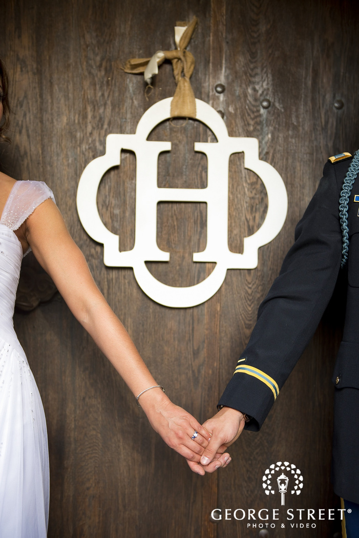 bride and groom hands under H monogram