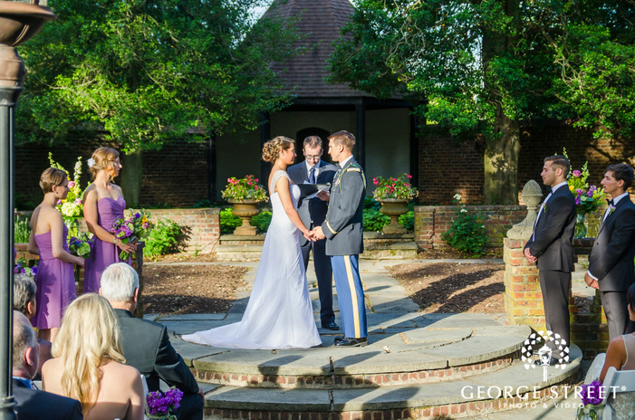bride and groom holding hands at outdoor stone courtyard wedding ceremony