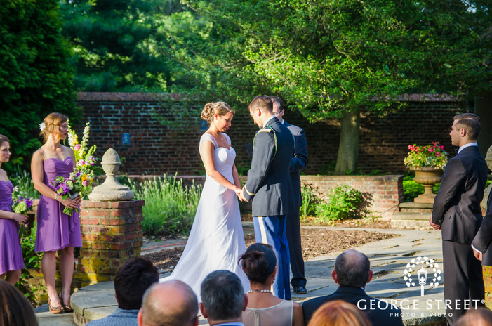 bride and groom holding hands at outdoor sunny courtyard wedding ceremony