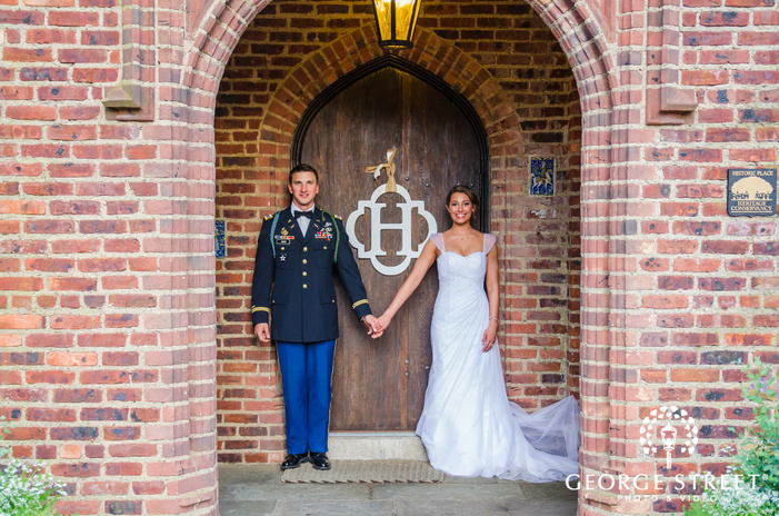bride and groom holding hands by H monogram under brick archway