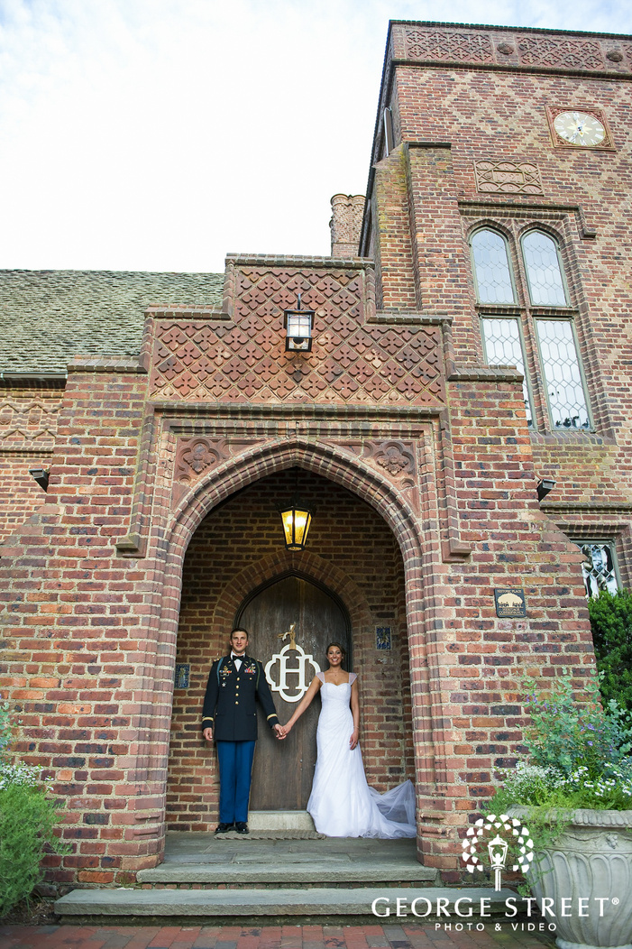 bride and groom holding hands posing in brick mansion archway