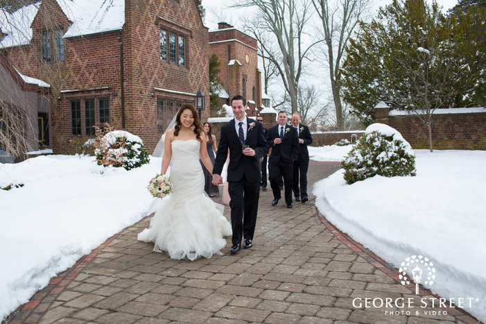 bride and groom holding hands walking through snowy courtyard with bridal party